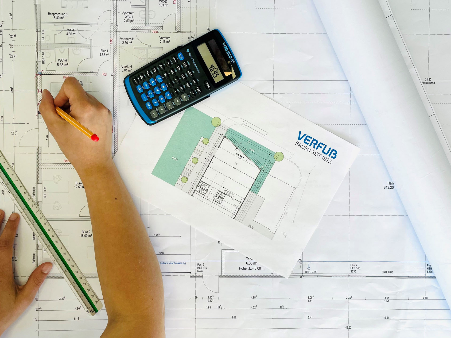 Bauzeichner bearbeitet einen Bauplan eines Mehrfamilienhauses