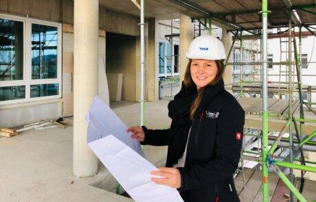 Bauleiterin steht in einer Baustelle prüft anhand eines Plans den Stand eines Bauprojekts