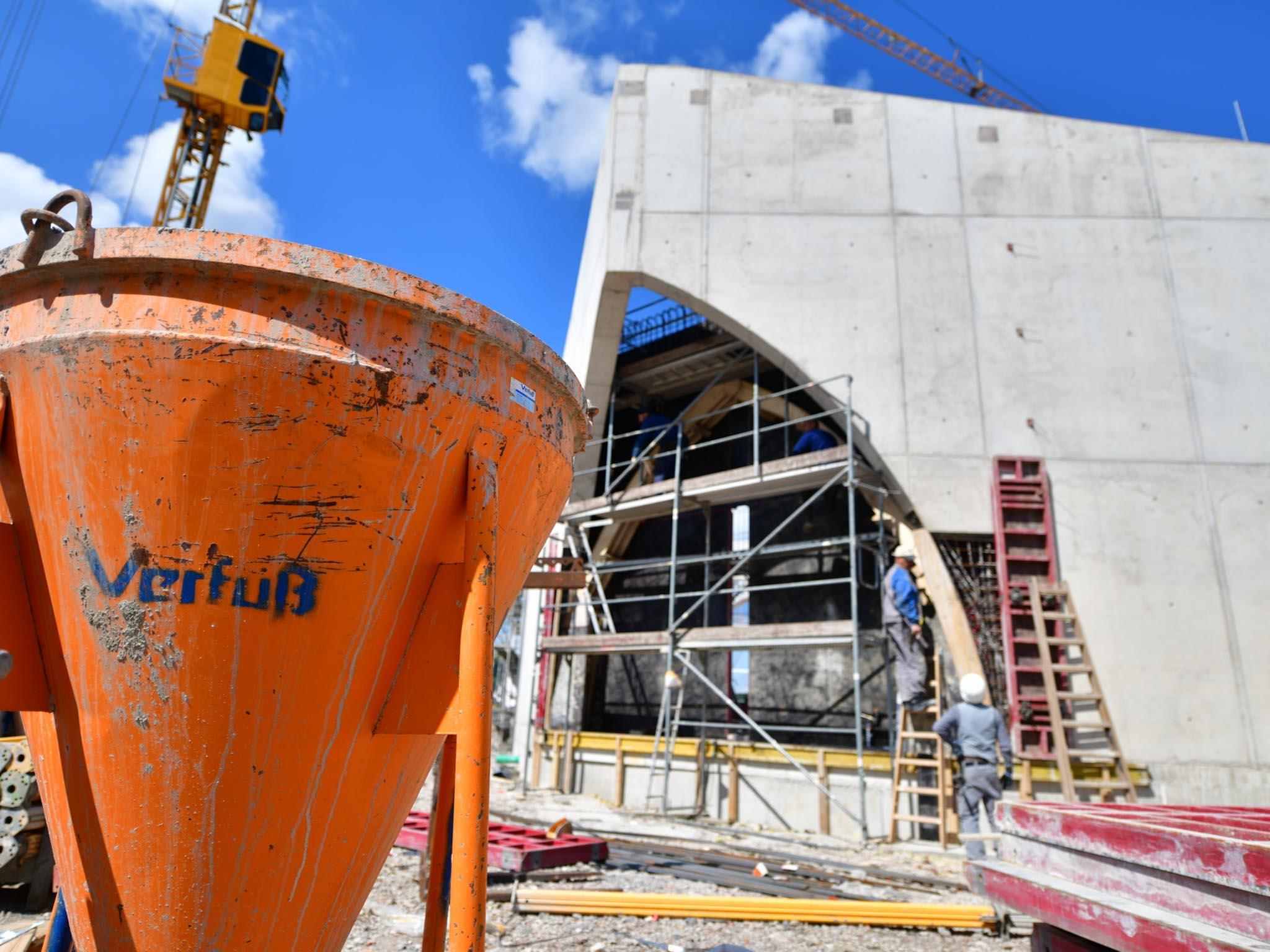 Betonsilo für den Hochbau vor einer Betonfassade eines Rohbaus