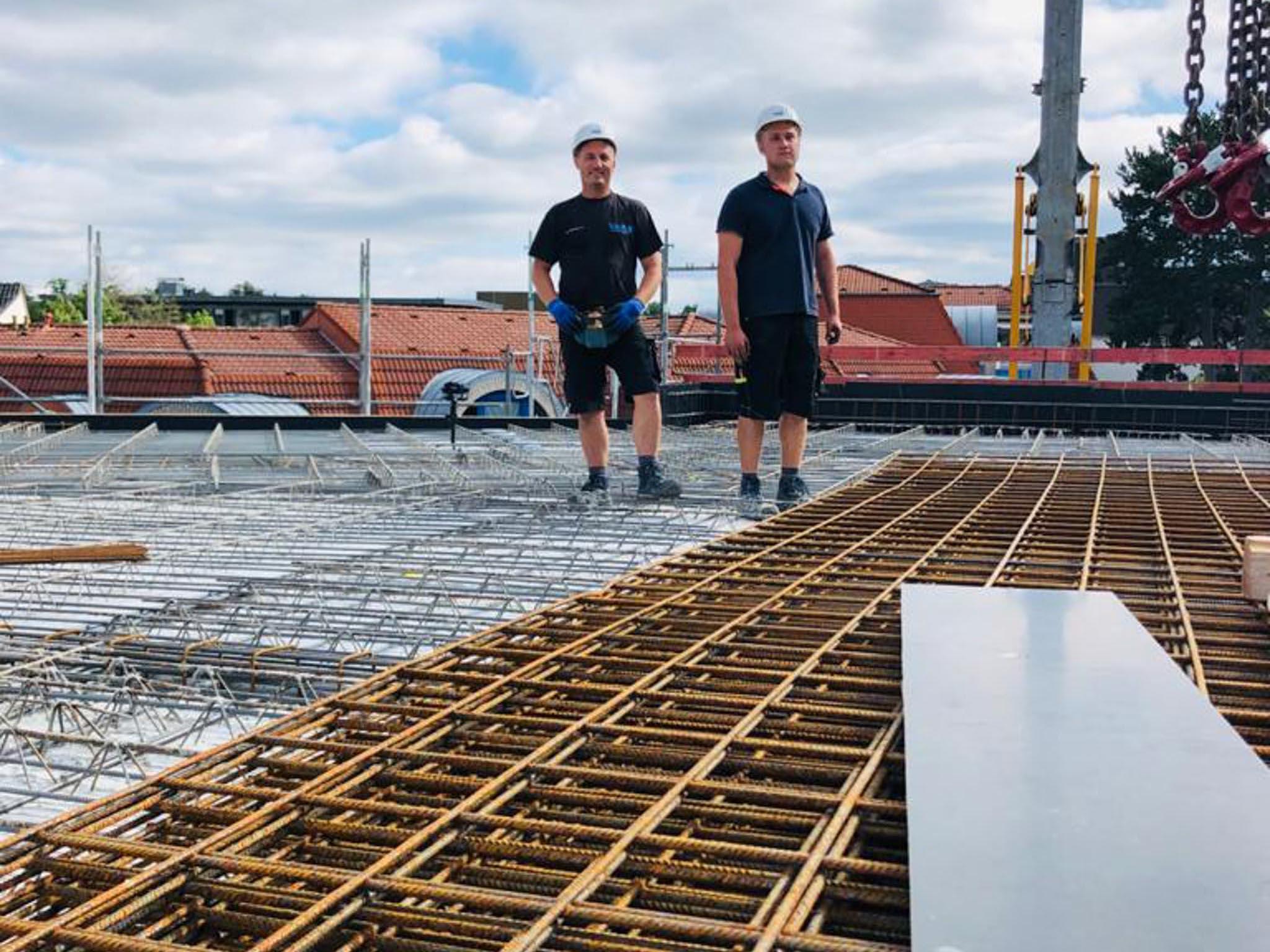 Zwei Stahlbetonarbeiter bereiten die Stahlmatten für eine Zwischendecke vor